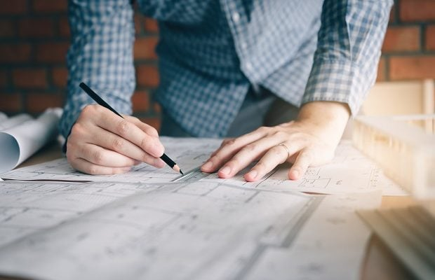 interior designer or architect reviewing blueprints and holding