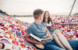 young hipster couple reading books in a hammock at the beach at