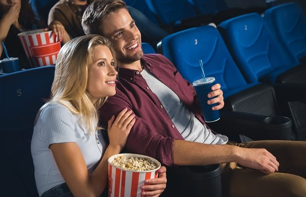 smiling couple with popcorn and soda drink watching film together in cinema