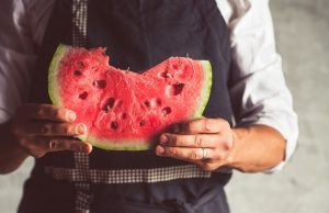 a man in a holding a big piece, striped watermelon. ripe delicious berry. vintage agricultural.