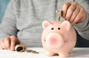 man puts money in piggy bank on white wooden table, space for te