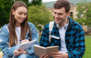 happy girl writing in notebook near handsome student reading book