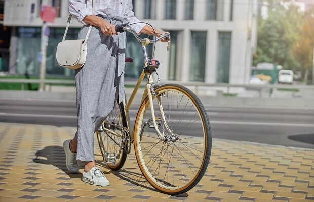 female tourist walking in the famous place of city with bike
