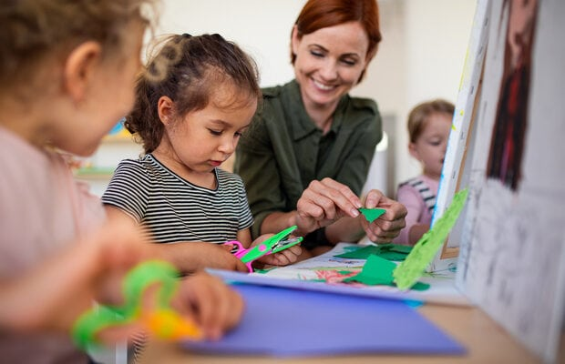 group of small nursery school children with teacher indoors in classroom, art and craft concept.