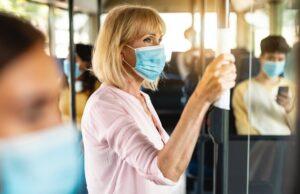 focused mature woman wearing medical mask taking bus