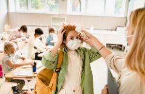 teacher measuring temperature on pupil`s forehead classmate schoolgirl before lesson