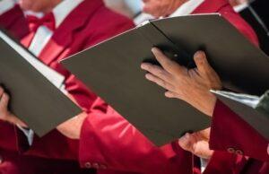 mens choir members holding singing book