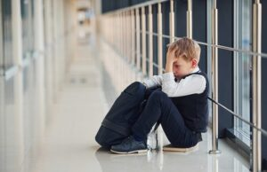 boy in uniform sitting alone with feeling sad at school. conception of harassment