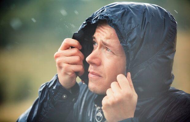man with dog in heavy rain