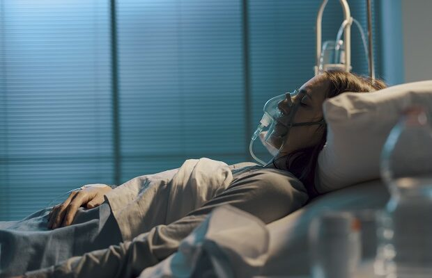 woman with oxygen mask lying in a hospital bed
