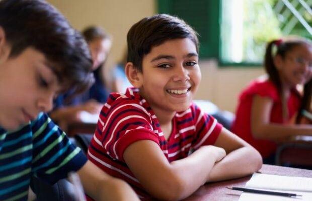 portrait of school boy looking at camera in class pkgs6vw