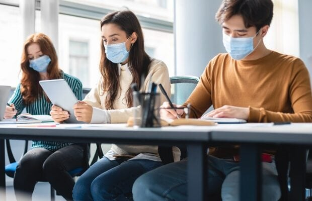 diverse students in masks sitting at desk in classroom