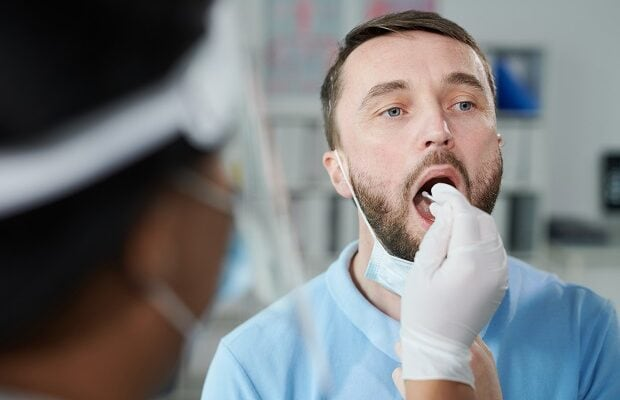 face of young male patient being tested for covid with oral swab by gloved nurse